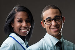 Couple of afro-american doctors on dark background. Couple of medical doctors smiling at the camera; young women and young men of african descent Stock Photo