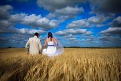 Couple against blue sky among rye fertility simbol Royalty Free Stock Photo