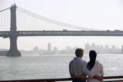 Couple Against The River And Brooklyn Bridge Stock Photos