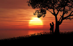 Couple against a sunset sky Stock Photography