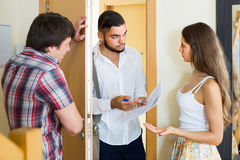 Couple with agent at doorway Royalty Free Stock Photos
