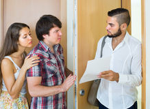 Couple with agent at doorway Stock Images