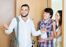 Couple with agent looking round new apartment. Happy couple stands with agent in the doorway looking round new apartment Royalty Free Stock Photos