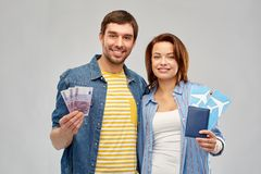 Couple with air tickets, passport and money. Travel, tourism and vacation concept - happy couple with air tickets, passport and money over grey background royalty free stock images