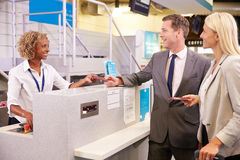 Couple At Airport Check In Desk Leaving On Business Trip Royalty Free Stock Photos