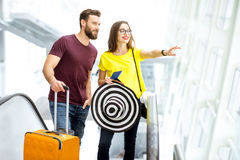 Couple at the airport. Young happy couple getting up with baggage on the escalator to the departure area of the airport during their summer vacation Stock Photos