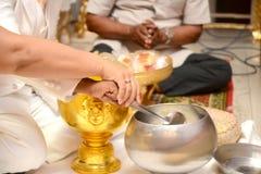 Couple alms to the Buddhist monks. Couple alms to the Buddhist monks at Thai wedding ceremony in Thailand stock photos