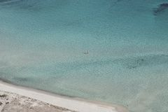 Couple alone in amazing turquoise waters, Sardinia. A suggestive and emotional image of a couple relaxing alone on amazing turquoise Sardinian waters. Image royalty free stock photos