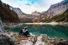 Couple on alpine lake shore Stock Images