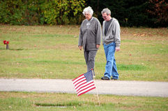 Couple in American cemetery. Senior couple walking in cemetery with American flag in foreground Stock Image