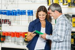 Couple Analyzing Product In Hardware Store. Happy couple analyzing product in hardware store Royalty Free Stock Photography