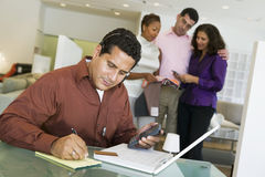 Couple And Salesperson With Man And Laptop In Foreground Stock Photography
