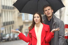 Couple annoyed in a rainy day. Portrait of a disgusted couple annoyed in a rainy day under the rain and an umbrella in winter royalty free stock image