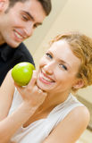 Couple with apple at home stock photography