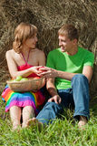 Couple with apples sitting on the grass hay Stock Photo