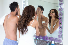 Couple applying cream on face while looking in mirror. At bathroom stock photo