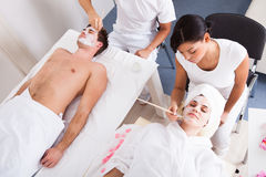 Couple Applying Facial Mask Stock Image