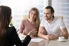 Couple applying for mortgage, taking bank loan to buy property. Family couple meeting with female real estate agent to choose property for buying or renting Stock Image