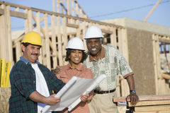 Couple And Architect In Front Of Incomplete House Stock Photography