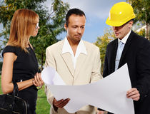 Couple and architect outdoors. Married couple and architect looking to the blueprint and discussing about the house construction plan Royalty Free Stock Photography