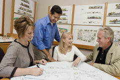 Couple And Architects Discussing Plan For New House Royalty Free Stock Photography