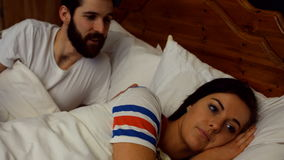 Couple arguing on bed in bedroom. At home stock video footage