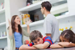 Couple arguing behind their children stock image