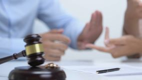Couple arguing in court, gavel with engagement rings on table, divorce concept. Stock footage stock footage