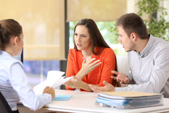 Couple arguing in a marriage consultory. Angry couple arguing telling their problems sitting in a desktop of a marriage counseling or office Royalty Free Stock Photography