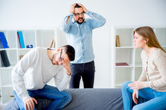 Couple arguing in a marriage counseling. Couple arguing and breaking up in a marriage counseling and driving therapist crazy Royalty Free Stock Photos