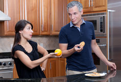 Couple arguing over diet. A young attractive couple arguing over junk food and healthy diets and nutrition Royalty Free Stock Photo