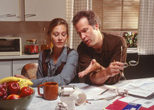 Couple arguing over finances. Married couple arguing in kitchen with financial papers on counter