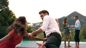 Couple arguing poolside during garden party. In slow motion stock video