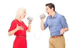 Couple arguing through a tin can phone Royalty Free Stock Photos
