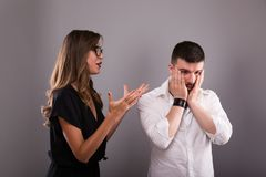 Couple arguing. Young woman speaking emotionally, blaming man, gesturing, explaining opinion. Unhappy girlfriend shouting to frust Stock Photos