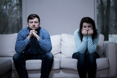 Couple after argument. Sitting on the sofa stock photography