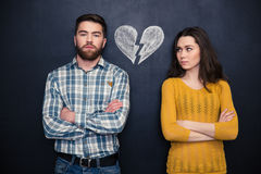 Couple after argument standing separately over blackboard background. Portrait of young couple after argument standing separately with hands folded over royalty free stock photo