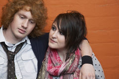 Couple With Arm Around Against Brick Wall Stock Image