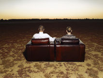 Couple On Armchairs Watching Sunset In Open Plain Stock Photos