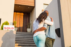 Couple with arms above after buying house Royalty Free Stock Photos