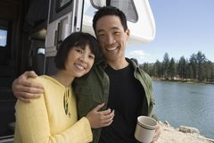 Couple with arms around each other outside RV at lake Stock Images