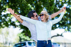 Couple with arms outstretched against trees Stock Photo