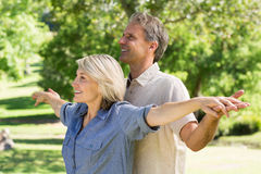 Couple arms outstretched in park Stock Photos