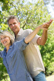 Couple with arms outstretched in park Royalty Free Stock Photography