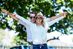 Couple with arms outstretched standing on street Stock Photo
