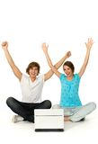 Couple with arms raised. Couple with laptop, sitting on floor Stock Photography