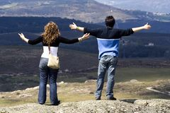 Couple with arms wide open. Appreciating landscape Stock Images