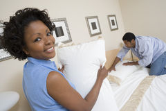Couple Arranging Bed At Home Royalty Free Stock Image