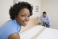 Couple Arranging Bed At Home. Portrait of an African American couple arranging bed at home royalty free stock images