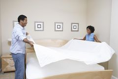 Couple Arranging Bedsheet Stock Image
